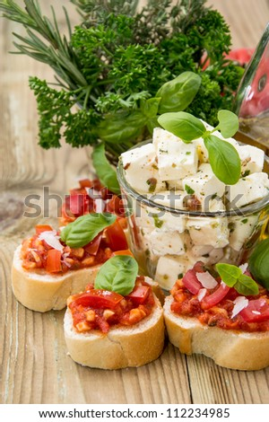Bruschetta with Feta Cheese against wooden background - stock photo