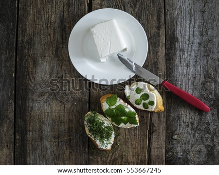 bruschetta with feta cheese and chopped spicy herbs on an old wooden weathered table