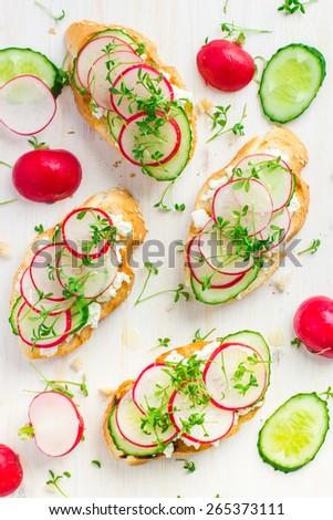 bruschetta with feta cheese, radish and cucumber on white background, top view - stock photo