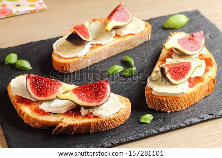 Bruschetta with figs, goat cheese and caramelized tomatoes - stock photo