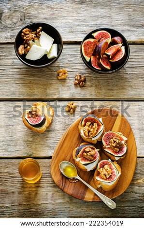 bruschetta with figs, honey, goat cheese and walnuts on a dark wood background. tinting. selective focus on walnut on the left bruschetta - stock photo