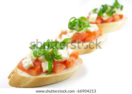 Bruschetta with fresh diced tomatoes, mozzarella and fresh basil isolated on white - Shallow DOF - stock photo