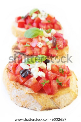 Bruschetta with fresh vine tomatoes, olives, fetta cheese, and basil, on crostini.  Shallow DOF. - stock photo