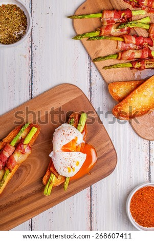 Bruschetta with grilled asparagus, bacon and poached eggs. - stock photo