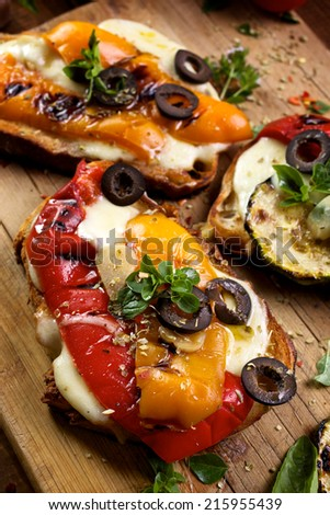 Bruschetta with grilled bell pepper, mozzarella cheese and herbs - stock photo