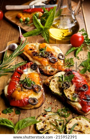Bruschetta with grilled bell pepper, zucchini, mozzarella cheese and herbs - stock photo