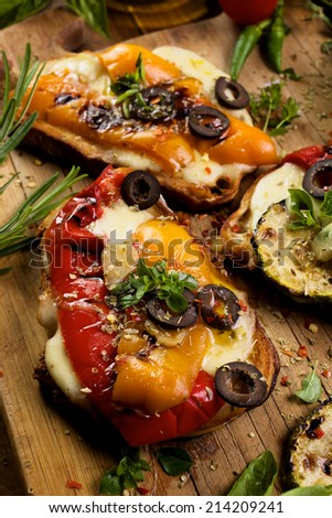 Bruschetta with grilled bell pepper, zucchini, olives and mozzarella cheese.  - stock photo