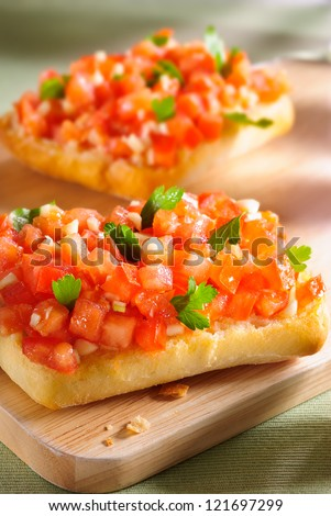 Bruschetta with grilled ciabatta, olive oil, chopped tomato, garlic and parsley leaves on wooden board
