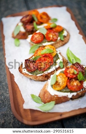Bruschetta with half dried tomatoes and basil - stock photo