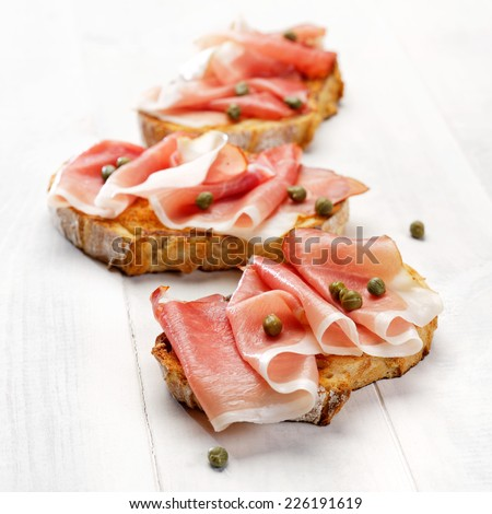 Bruschetta with ham and capers - stock photo