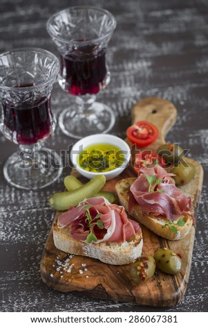bruschetta with  ham, olives, cherry tomatoes in olive Board and red wine on a dark wooden background - stock photo
