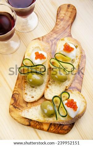bruschetta with mozzarella, green olives, zucchini & red caviar. red vine.  - stock photo