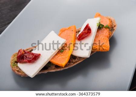 Bruschetta with pumpkin, feta cheese and tomatoes - stock photo