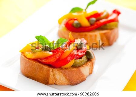 Bruschetta with roasted bell pepper,capers and basil - stock photo