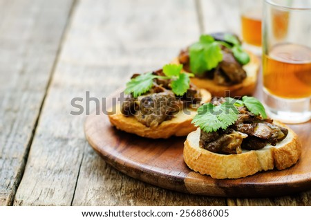 bruschetta with roasted mushrooms on a dark wood background. tinting. selective focus