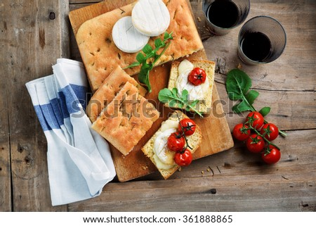 Bruschetta with stewed tomatoes and cheese Tomino.  Italian healthy breakfast with focaccia - stock photo