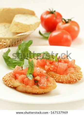 Bruschetta with tomato and basil on white plate