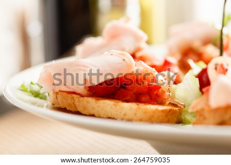 Bruschetta with tomato and ham - stock photo