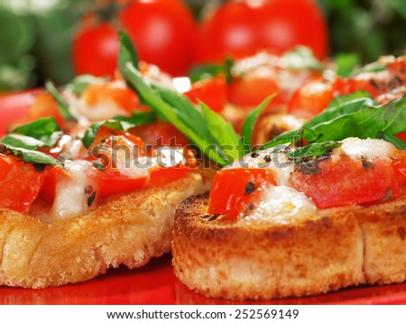 Bruschetta with tomato and mozzarella cheese, decorated with basil - stock photo