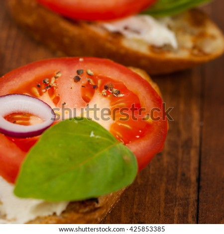 Bruschetta with Tomato, Cream Cheese and Basil. Selective focus. - stock photo