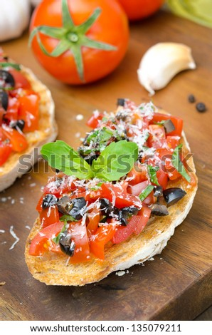 bruschetta with tomato, olives, basil and cheese on a wooden board - stock photo