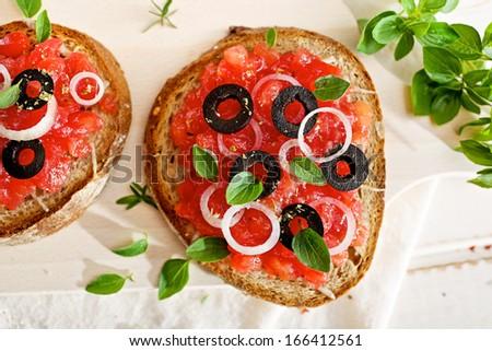 Bruschetta with tomato, onion, olives and oregano - stock photo