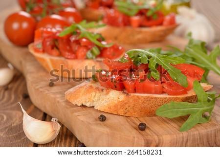 Bruschetta with tomatoes and arugula - stock photo