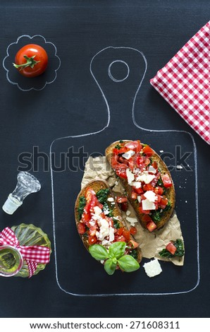 Bruschetta with tomatoes and spinach, parmesan and pesto sauce - stock photo