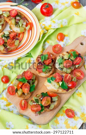 Bruschetta with zucchini, bacon, green onions and cherry tomatoes - stock photo
