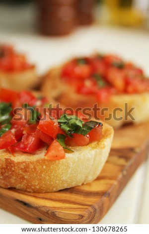 Bruschettas with basil on wooden board for appetizer