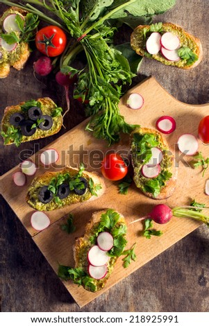 Bruschettas with pesto sauce and vegetables from above - stock photo