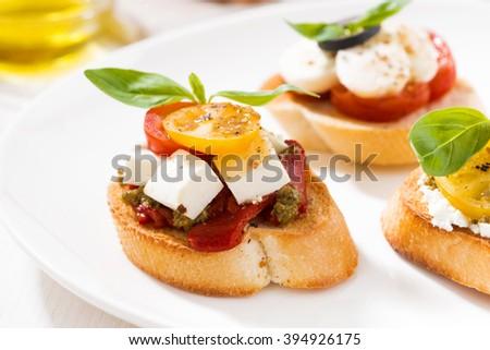 bruschettas with tomatoes and mozzarella on plate, closeup, horizontal - stock photo