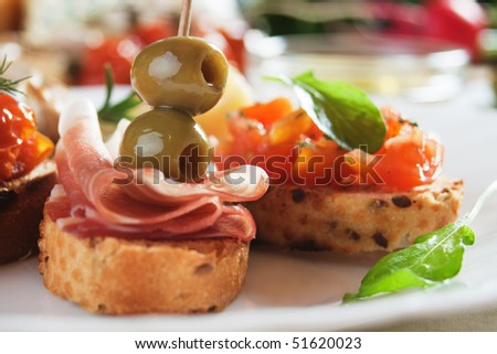 Bruschette, italian toasted bread with prosciutto and olives