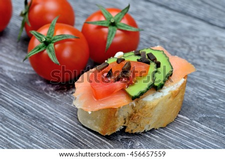 bruschette salmon and tomato on gray wooden table