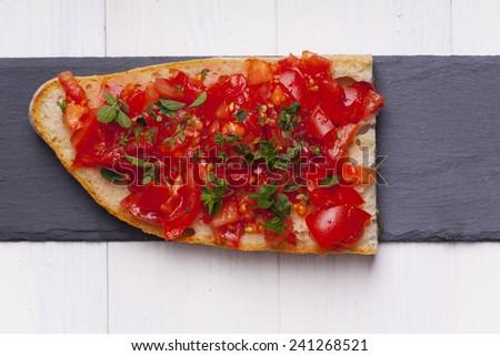 bruschette with oregano on slate  - stock photo