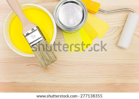 brush and roller with color samples and paint can on wooden background - stock photo