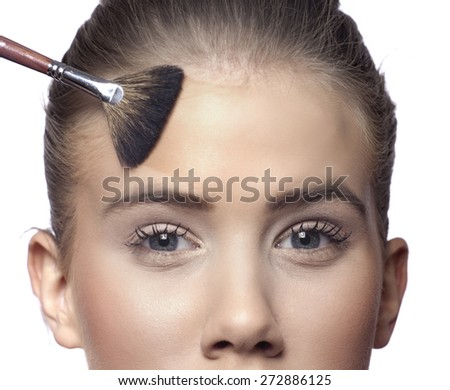 Brush blusher spreading liquid cosmetic powder on face and eyes with powder line - stock photo