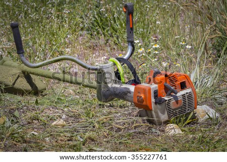 brush cutter, cutting weeds in a garden - stock photo