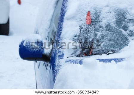 Brush for cleaning car from snow lying on windscreen, concept of transportation and winter - stock photo