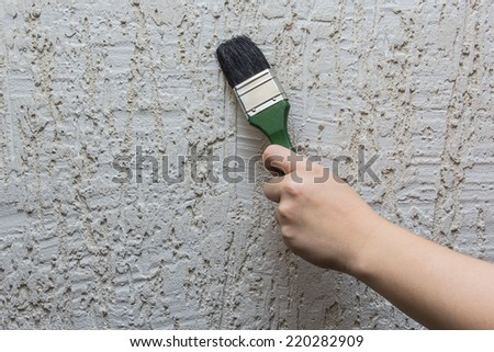 Brush in hand on background of wall with plaster - stock photo