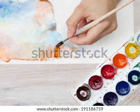 brush in the hands of the artist, watercolor painting, creativity - stock photo