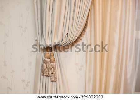 Brush on the curtains in beige room - stock photo