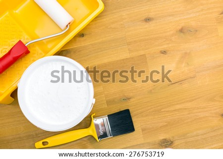 brush, roller in tray and paint can on wooden background - stock photo