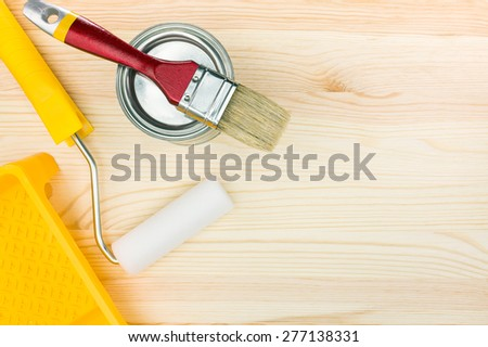 brush, roller in tray and paint tin can on wooden background - stock photo