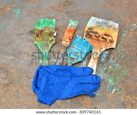 brush to paint in different colors and gloves - stock photo