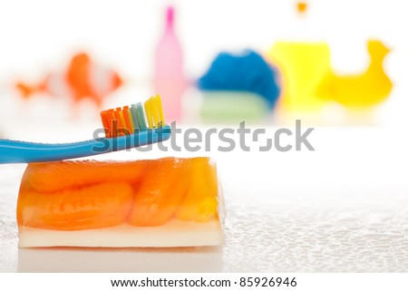Brush your teeth every day - kids tooth brush with toys and bath accessories on background - stock photo