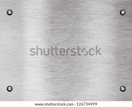 Brushed silver shiny metallic surface with bolts - stock photo