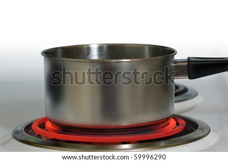 Brushed steel pot on red hot electric stove - stock photo