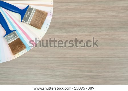 Brushes and color guide on oak background - stock photo