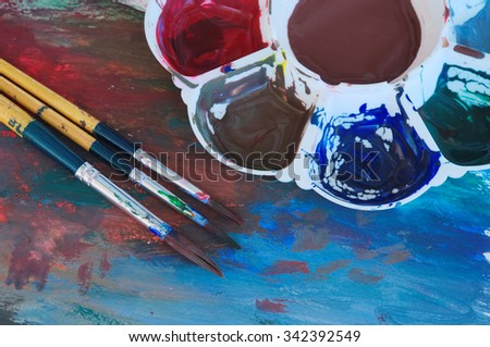 brushes and color palette with paint, close up. - stock photo